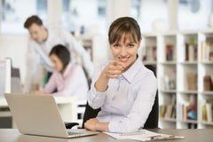 指向一个手指的俏丽的女实业家在办公室,看照相机 免版税库存图片