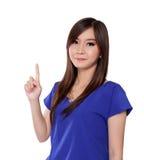 指向一个手指的年轻亚裔妇女,隔绝在白色 免版税库存图片