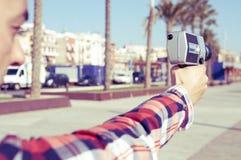 指向一台减速火箭的影片照相机的年轻人 免版税库存照片