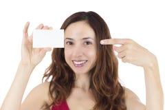 指向一张空白的名片的微笑的妇女 免版税库存照片
