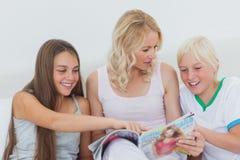 指向一本杂志的女孩在她的母亲手上 免版税库存照片