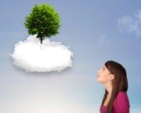 指向一棵绿色树的女孩在一朵白色云彩顶部 图库摄影