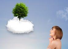 指向一棵绿色树的女孩在一朵白色云彩顶部 免版税图库摄影