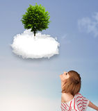 指向一棵绿色树的女孩在一朵白色云彩顶部 库存照片