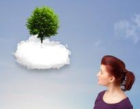 指向一棵绿色树的女孩在一朵白色云彩顶部 库存图片