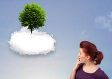 指向一棵绿色树的女孩在一朵白色云彩顶部 免版税库存照片