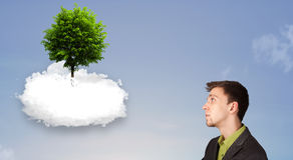 指向一棵绿色树的年轻人在一朵白色云彩顶部 库存图片