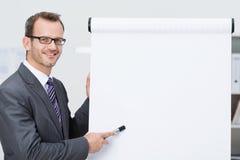 指向一空白的flipchart的微笑的商人 免版税图库摄影