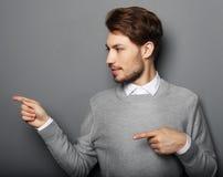 指向与他的手指的一个年轻和英俊的商人 免版税库存照片