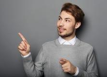 指向与他的手指的一个年轻和英俊的商人 库存图片