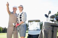 指向与后边高尔夫球儿童车的愉快的打高尔夫球的夫妇 库存图片