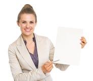 指向与在白纸板料的笔的愉快的女商人 免版税库存照片