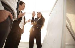 指向与在flipchart的一个标志的女商人 库存图片
