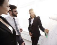 指向与在flipchart的一个标志的女商人 免版税库存照片