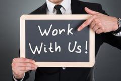 指向与我们的商人工作在板岩的标志 免版税库存照片
