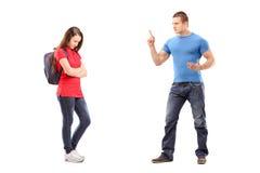 指向与手指和威胁在他的姐妹的恼怒的兄弟 免版税图库摄影