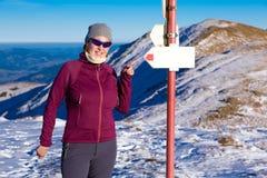指向与手指的女性远足者道路签到冬天山 库存照片