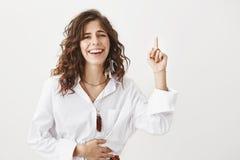 指向与食指的感情可爱的白种人女性画象,当握在腹部和笑时的手 免版税图库摄影