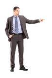 指向与他的f的一个恼怒的商人的全长画象 免版税库存照片
