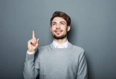 指向与他的手指的一个年轻和英俊的商人 免版税库存图片