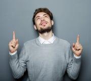 指向与他的手指的一个年轻和英俊的商人 库存照片
