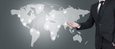 指向世界地图的商人 库存图片