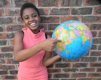 指向世界地球地图的非洲的微笑的女孩 免版税图库摄影