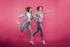 指向两个情感的女友跳跃和 免版税图库摄影