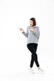 指向两个手指的一名偶然妇女的全长画象 免版税图库摄影