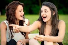 指向两名美丽的年轻人惊奇的妇女外面 库存照片