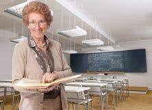 指向书的快乐的资深老师 免版税库存图片