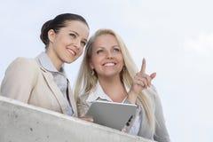 指向低角度的观点的愉快的女实业家,当站立与大阳台的工友反对天空时 图库摄影