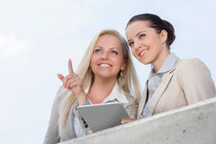 指向低角度的观点的愉快的女实业家,当站立与大阳台的工友反对天空时 免版税库存图片