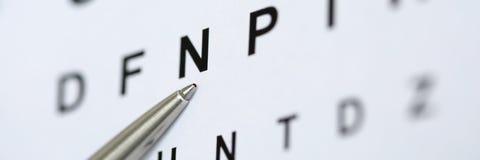 指向信件的银色圆珠笔在眼力检查桌里 库存图片