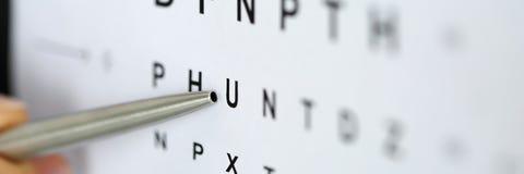 指向信件的银色圆珠笔在眼力检查桌里 库存照片