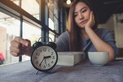 指向充满乏味的感觉的一个黑时钟的亚裔妇女,当等待某人时 库存照片