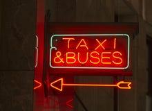 指向出租汽车公共汽车的红色霓虹灯广告室内标志箭头 库存照片