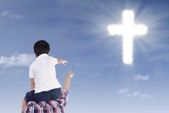 指向十字架的父亲和儿子 库存图片
