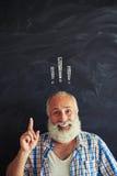 指向反对有惊叹号ins的黑板的老人 库存照片