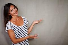 指向反对灰色背景的吸引人夫人 免版税库存照片