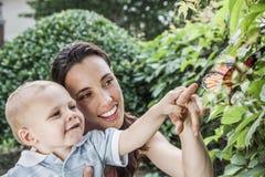 指向和看一只蝴蝶的微笑的母亲和儿子在庭院里 库存图片