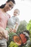 指向和看一只蝴蝶的微笑的母亲和儿子在庭院里 库存照片