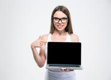 指向在一个空白的膝上型计算机屏幕上的微笑的女孩手指 库存图片