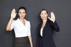 指向在一个虚屏的二名女实业家 库存照片