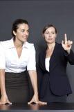 指向在一个虚屏的二名女实业家 免版税库存图片