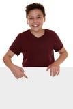 指向在与copyspace的一副空的横幅的年轻男孩或少年 库存照片