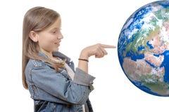 指向在世界地球的一个微笑的小女孩的画象手指 库存照片