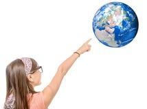 指向在世界地球的一个微笑的小女孩的画象手指 免版税库存照片