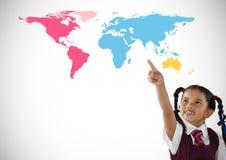 指向在五颜六色的世界地图前面的女小学生 库存照片