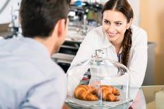指向在嘘咖啡的法国新月形面包的友好的女服务员 免版税库存图片